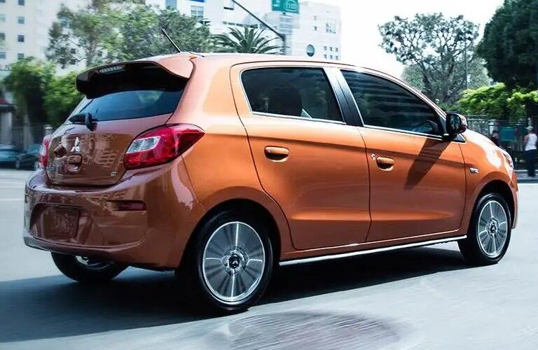 Rear passenger angle of an orange 2020 Mitsubishi Mirage driving in a city