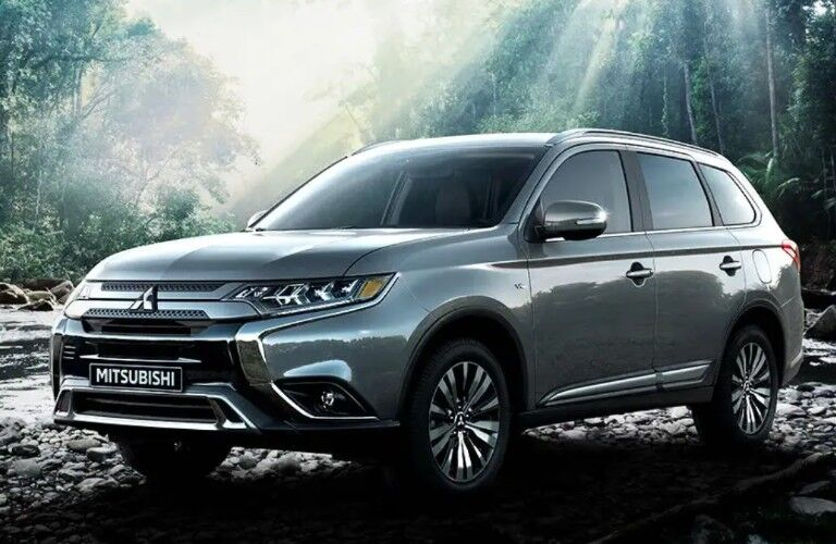 Front driver angle of a grey 2020 Mitsubishi Outlander parked in a forest