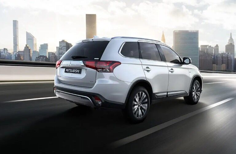 Rear passenger angle of a white 2020 Mitsubishi Outlander driving on a road with a city skyline in the background