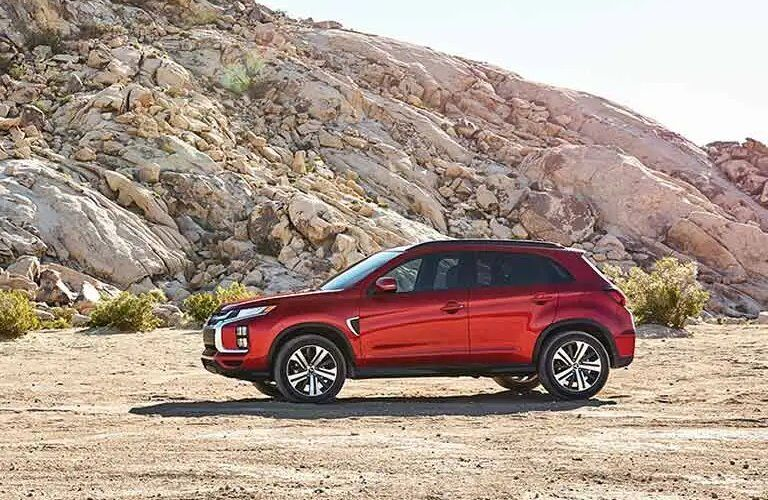 Driver angle of a red 2020 Mitsubishi Outlander Sport parked by a rocky cliff