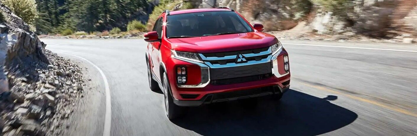 Front angle of a red 2020 Mitsubishi Outlander Sport driving down a road
