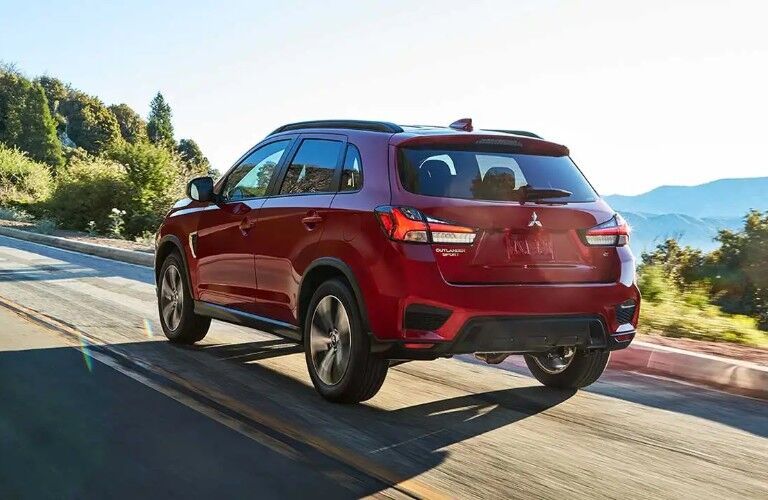 Rear driver angle of a red 2020 Mitsubishi Outlander Sport driving on a road