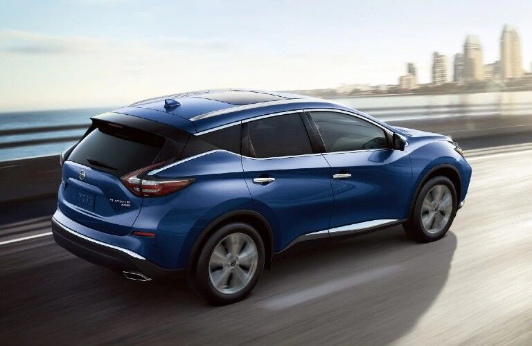Rear passenger angle of a blue 2020 Nissan Murano driving on a bridge