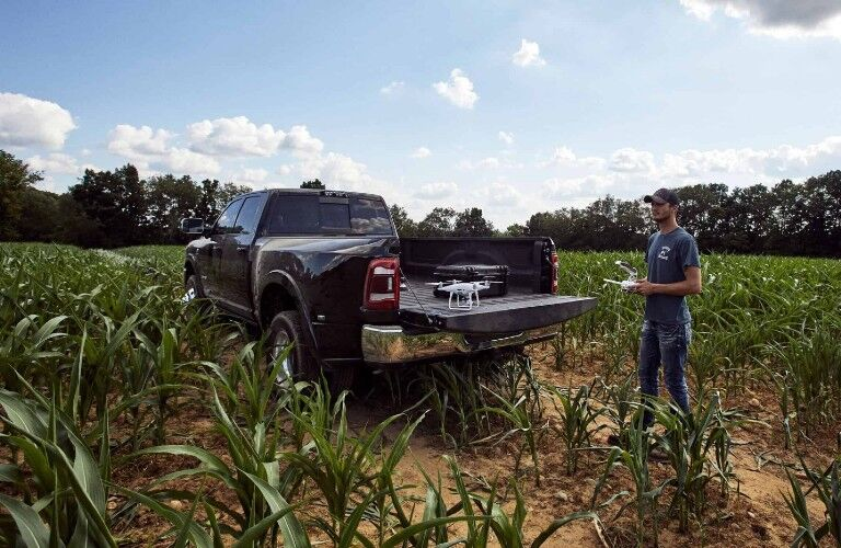Rear driver angle of a black 2020 RAM 3500 parked in a field with a man nearby