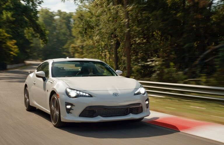 Front passenger angle of a white 2020 Toyota 86 driving on a road
