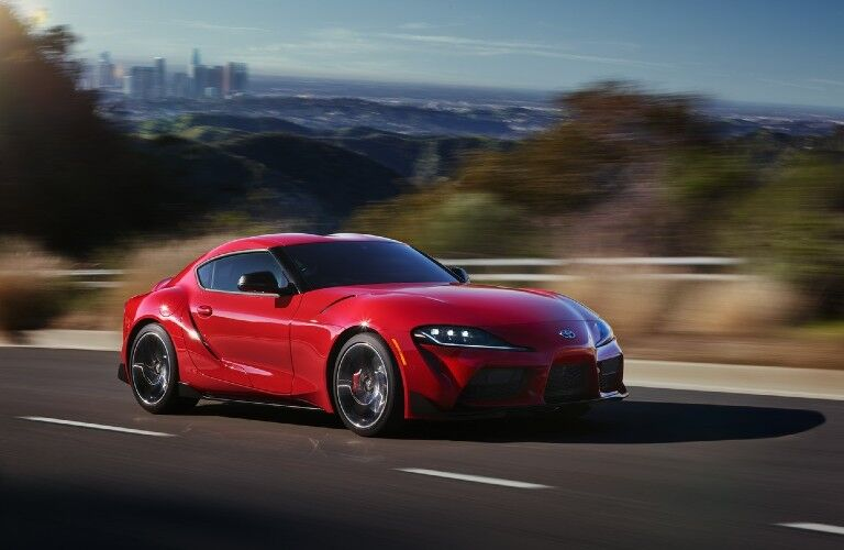 Front passenger angle of a red 2020 Toyota GR Supra driving on a road