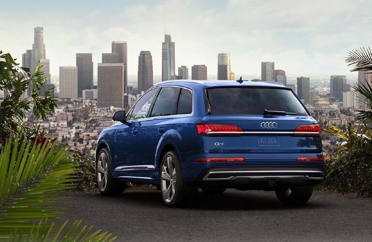 Rear driver angle of a blue 2021 Audi Q7 parked in front of a city