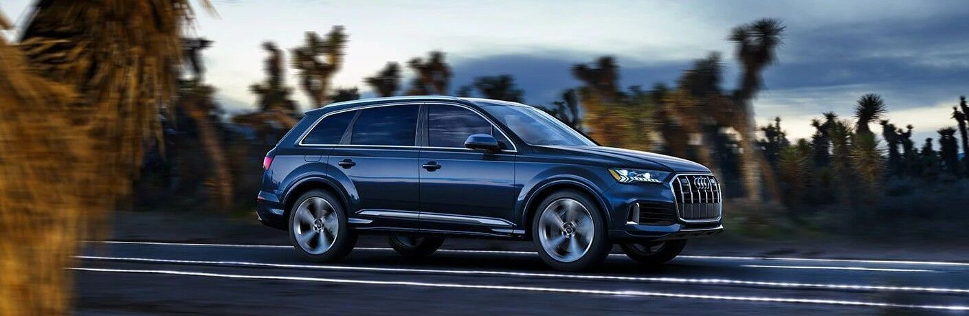 Front passenger angle of a blue 2021 Audi Q7 driving on a road