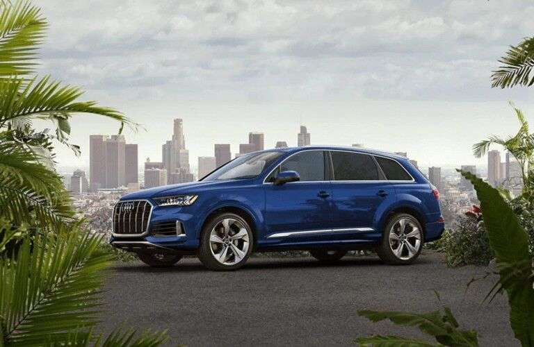 Front driver angle of a blue 2021 Audi Q7 parked in front of a city