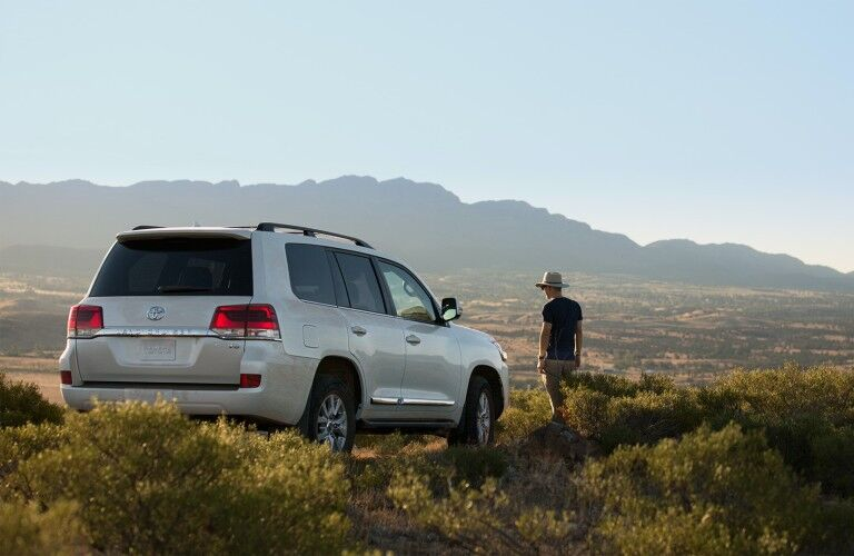 Rear passenger angle of a white 2021 Toyota Land Cruiser parked near mountains and a man standing near it