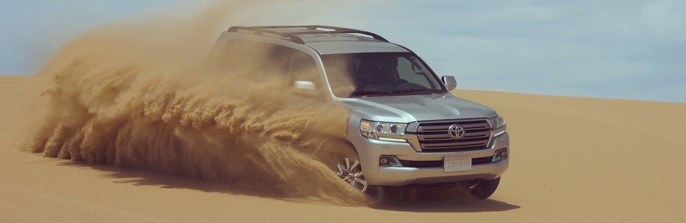 Front passenger angle of a silver 2021 Toyota Land Cruiser driving in sand
