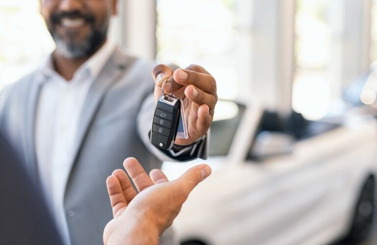 Happy car salesman handing over car keys