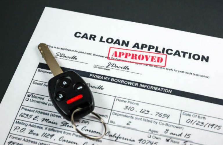 Car loan application with keys on top of it