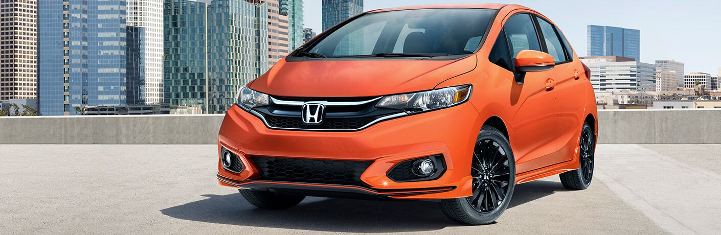 Front quarter side profile of the 2017 Honda Fit parked on top of a building with a cityscape in the background