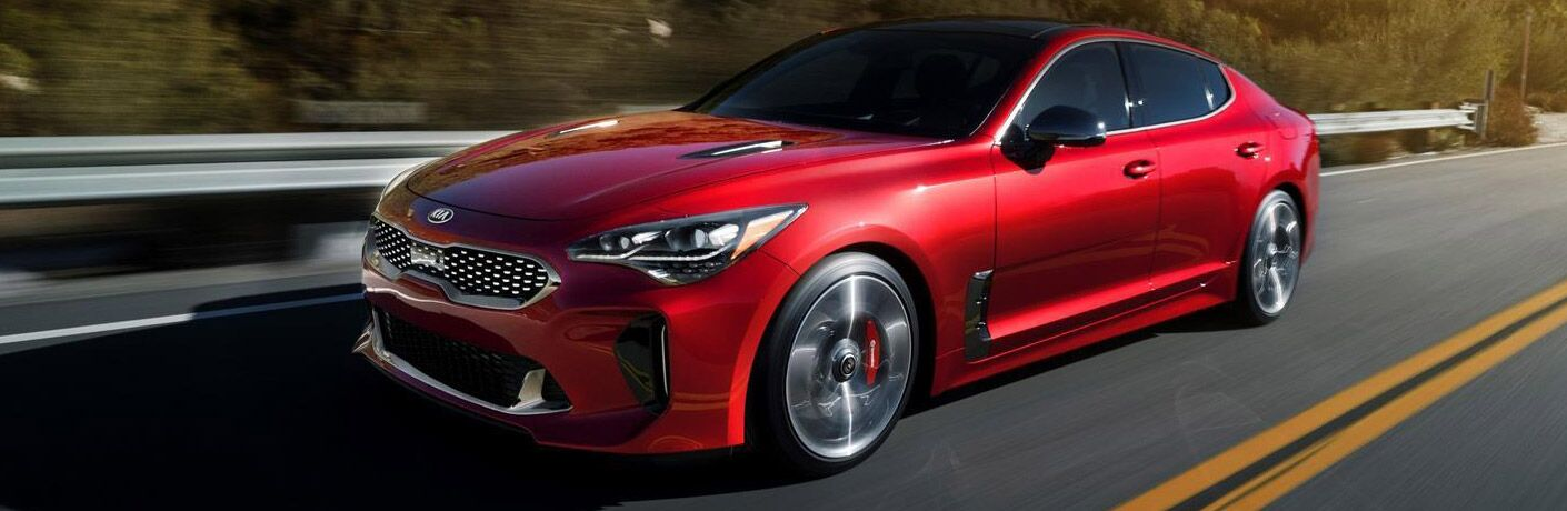 red kia stinger driving on a highway