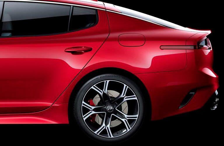 rear left side of red kia stinger, back tire, fuel door