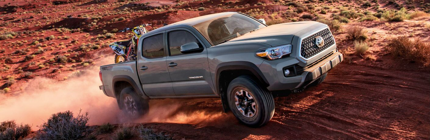 2018 toyota tacoma with dirtbike in back crawling over rocks and sand