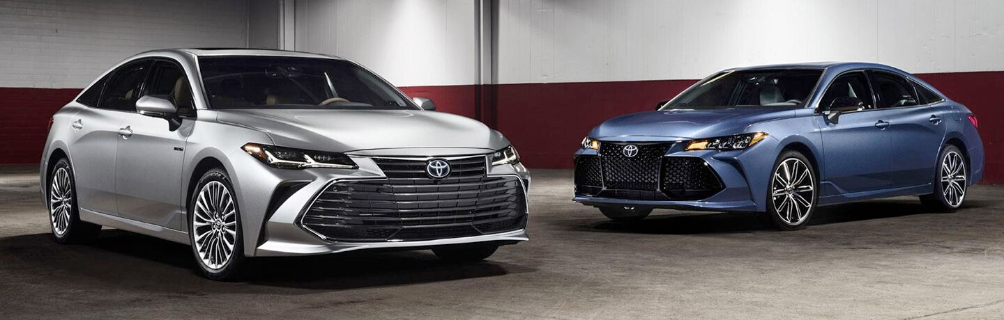 A silver and a blue 2019 Toyota Avalon sit in a garage.