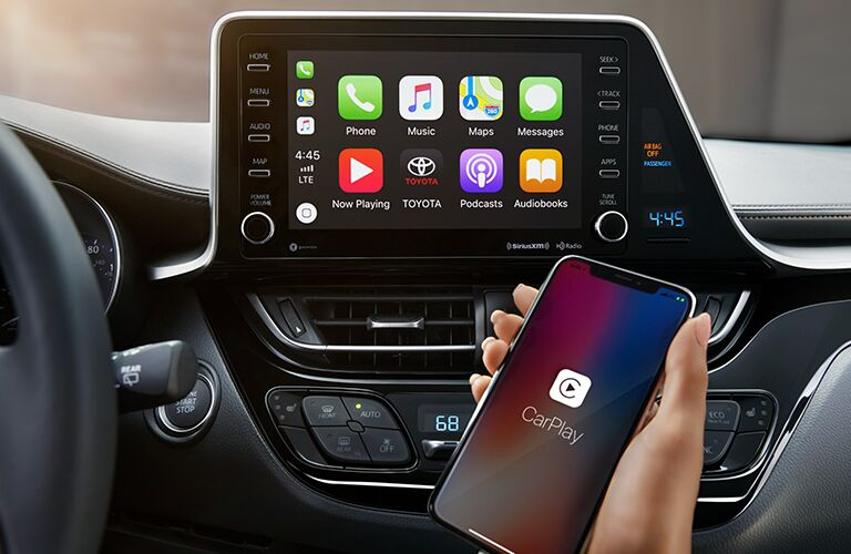 A woman holding a smartphone in front of the screen of the 2019 Toyota C-HR's infotainment display