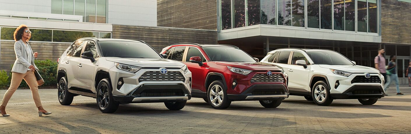 A row of three, 2019 Toyota RAV4 Hybrid models in a row outside a modern building
