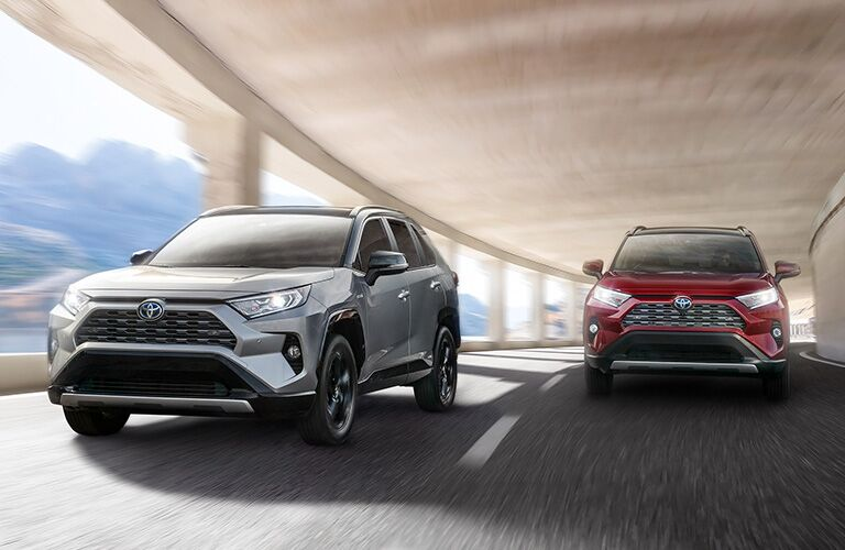 Two, 2019 Toyota RAV4 Hybrid models driving in a tunnel