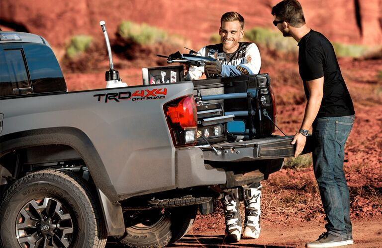 Two men load some implements in the bed of a 2019 Toyota Tacoma Off Road in the middle of a red desert.