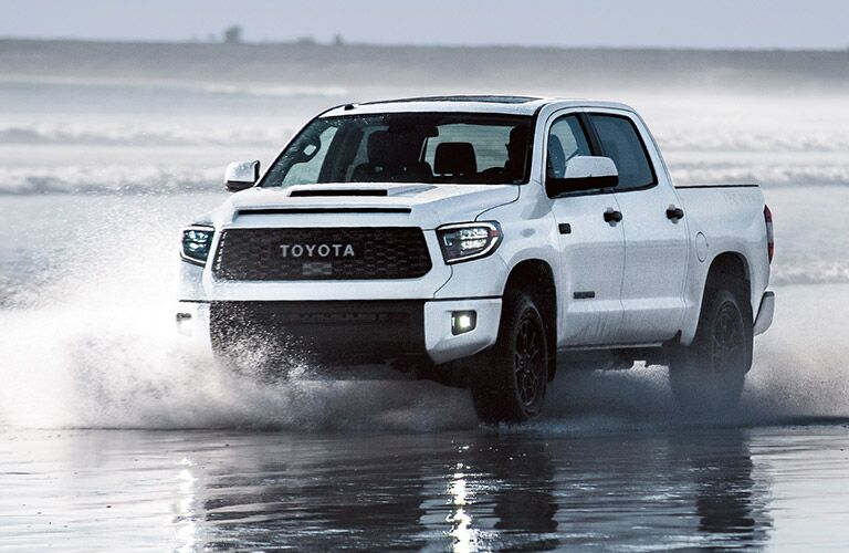 2019 Toyota Tundra drives through shallow water.