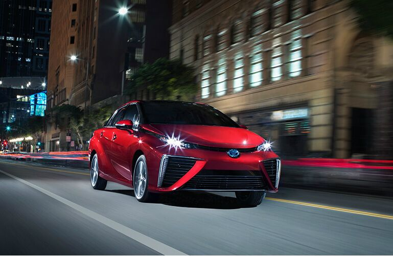 Red 2019 Toyota Mirai drives down a city street at night.