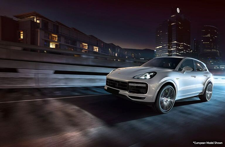 white 2020 porsche cayenne driving at night in merriam kansas