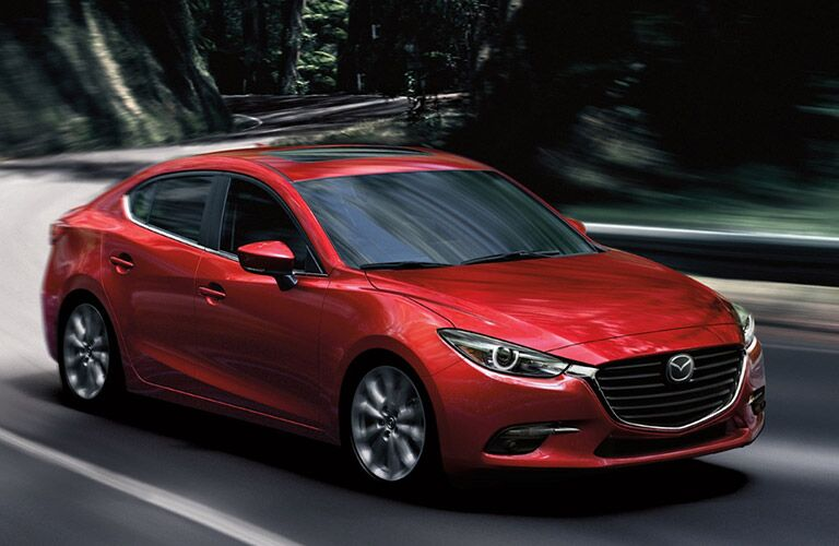 Exterior view of a red 2018 Mazda3 sedan driving down a country road with trees in background