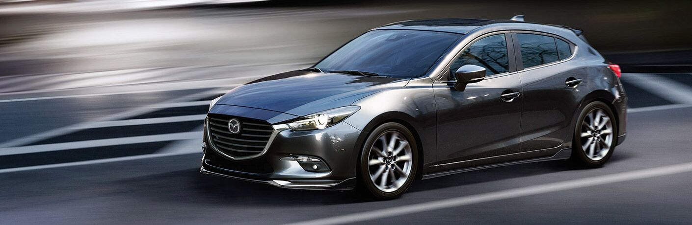 Exterior view of a grey 2018 Mazda3 Hatchback driving down a highway
