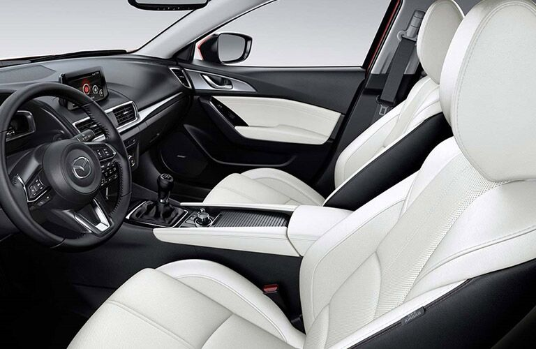 Interior view of a 2018 Mazda3 showing white and black seating and steering wheel