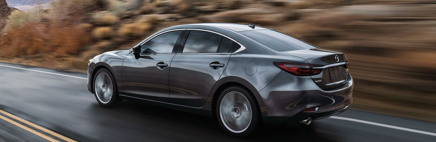 Exterior view of a gray 2019 Mazda6 driving down a country highway