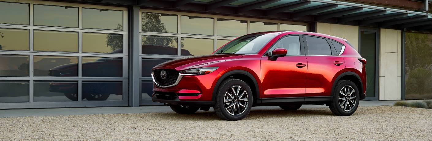 Exterior view of the driver's side of a red 2018 Mazda CX-5 parked outside a glass building