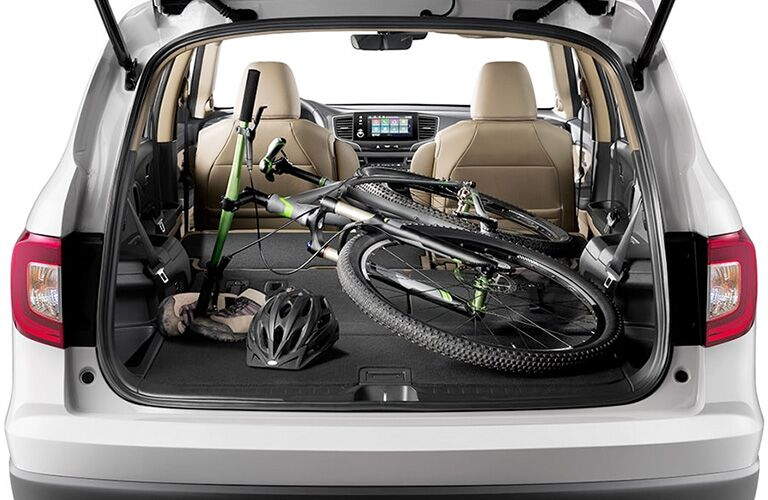 A bicycle and helmet are packed inside the opened rear cargo area of a 2020 Honda Pilot with the seats lowered.