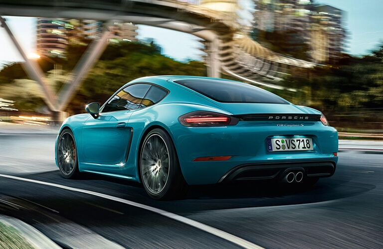 Rear driver angle of a blue 2019 Porsche 718 Cayman S driving down a road