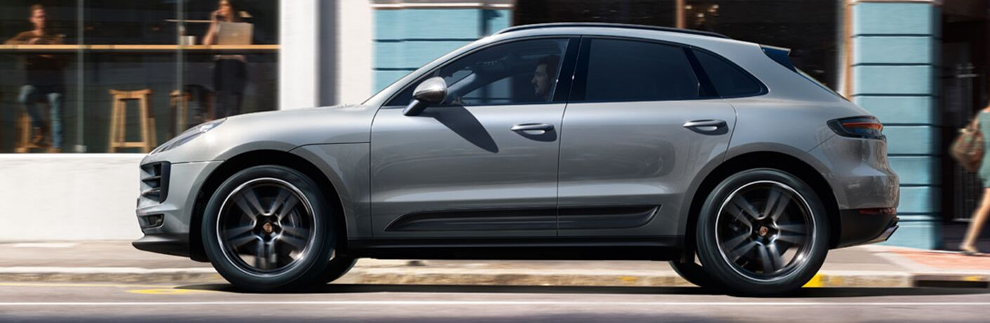 Profile view of man driving inside Porsche Macan