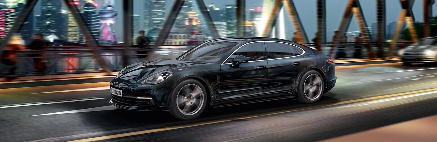 2019 Porsche Panamera exterior front fascia and drivers side going fast on blurred city bridge