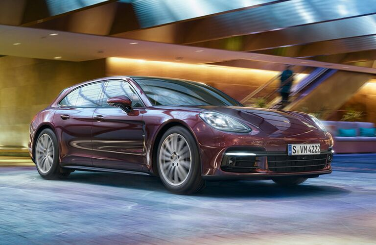 2019 Porsche Panamera exterior front fascia and passenger side driving fast inside building with person on stairs