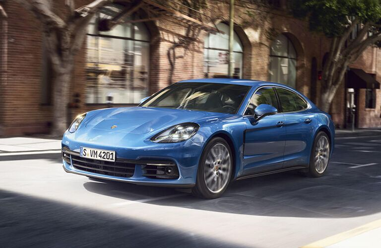 2019 Porsche Panamera exterior front fascia and drivers side driving fast next to blurred brick building