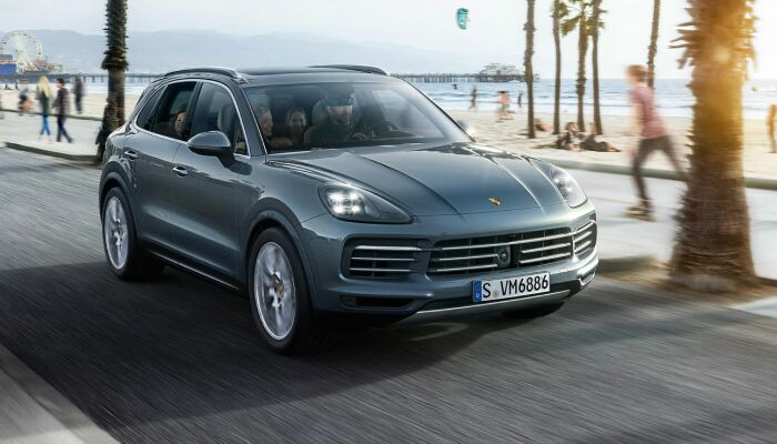 2019 Porsche Cayenne exterior front fascia and passenger side on beach with blurred person roller skating next to it