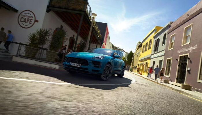 Blue Porsche Macan driving on city street
