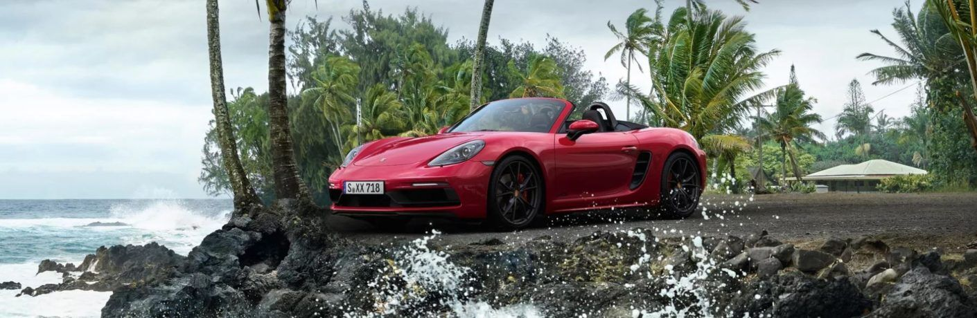 Red 2019 Porsche 718 Cayman GTS by beach and palm trees