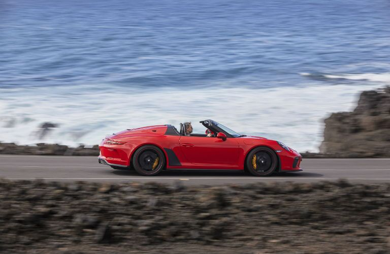 2019 Porsche 911 Speedster exterior passenger side profile going fast on blurred beach highway