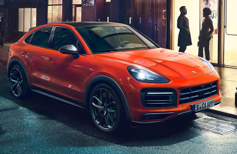 2020 Porsche Cayenne Coupe exterior front fascia and passenger side parked on road with people chatting in doorway of shop
