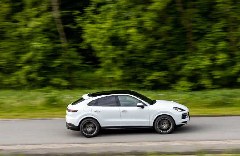 2020 Porsche Cayenne Coupe exterior passenger side going fast on highway with blurred trees