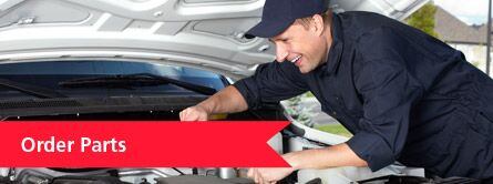"""Mechanic leaning over car with red """"order parts"""" banner to the left"""