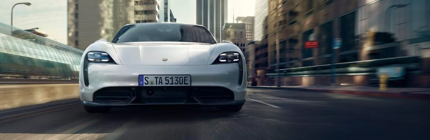 Front view of white 2020 Porsche Taycan driving through city