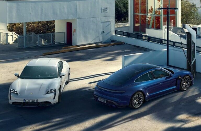 Two 2020 Porsche Taycan models at charging station