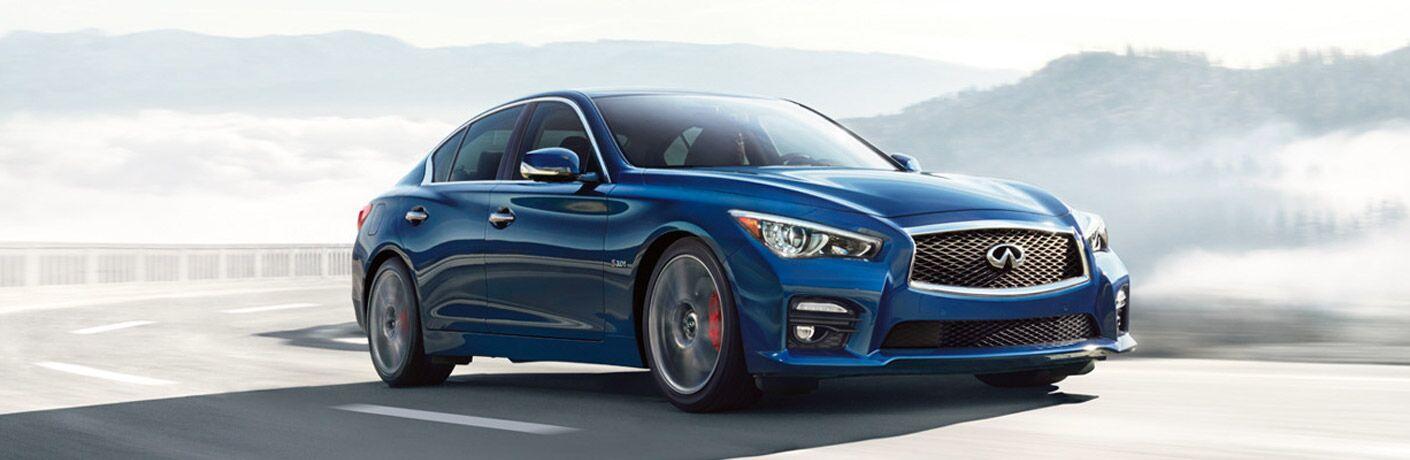 Blue 2019 INFINITI Q50 driving on a mountainous road